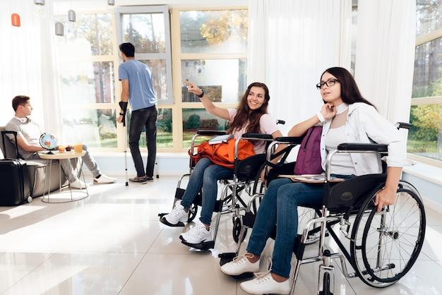 Duas lindas meninas em uma cadeira de rodas no saguão do aeroporto. Foto Premium