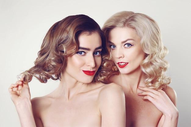 Duas lindas meninas fofoqueira com profissional make up e penteado Foto Premium