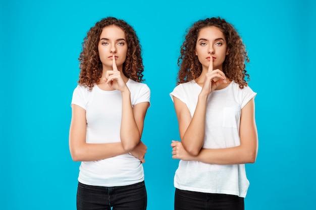 Duas lindas meninas gêmeas mostrando manter silêncio sobre parede azul Foto gratuita