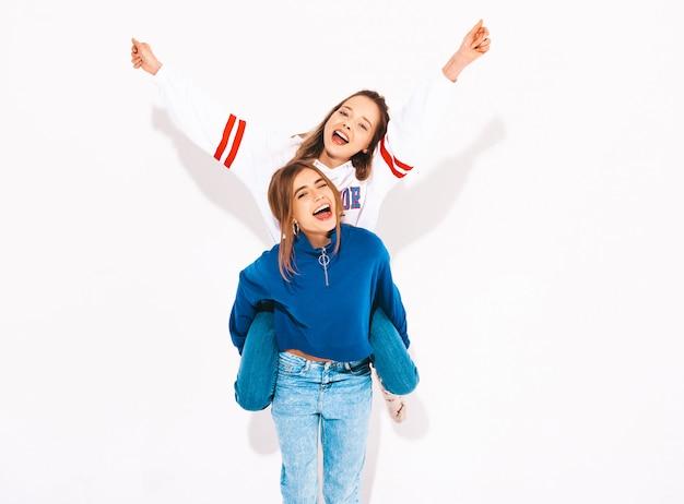 Duas lindas meninas sorridentes em roupas da moda no verão. mulheres despreocupadas. modelo positivo, sentado nas costas da amiga e levantando as mãos Foto gratuita