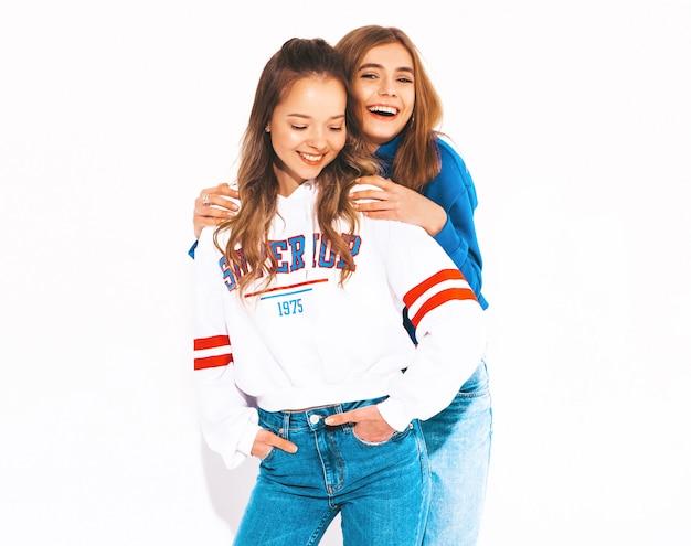 Duas lindas meninas sorridentes em roupas da moda no verão. mulheres despreocupadas. modelos positivos Foto gratuita