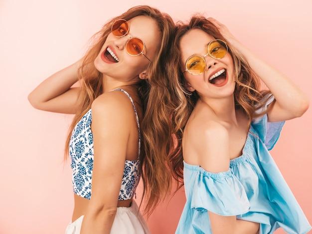 Duas lindas meninas sorridentes em roupas da moda no verão. mulheres sexy despreocupadas posando. modelos positivos se divertindo Foto gratuita