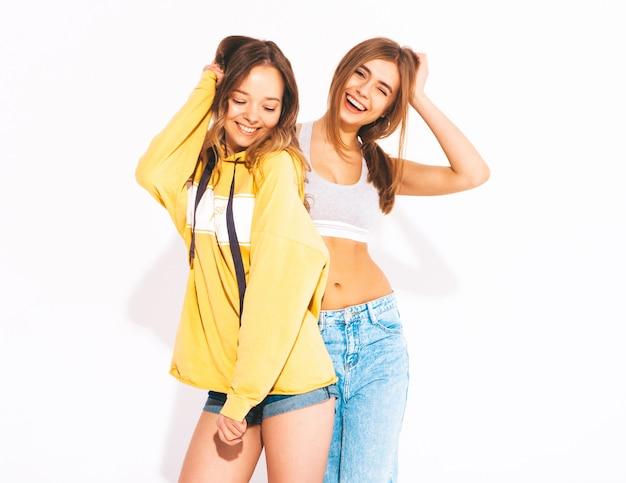 Duas lindas meninas sorridentes em roupas da moda verão jeans. mulheres sexy e despreocupadas. modelos positivos Foto gratuita