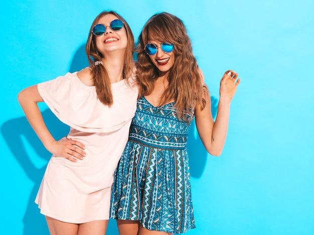 Duas lindas meninas sorridentes no verão na moda vestidos e óculos de sol. mulheres sexy despreocupadas posando. Foto gratuita