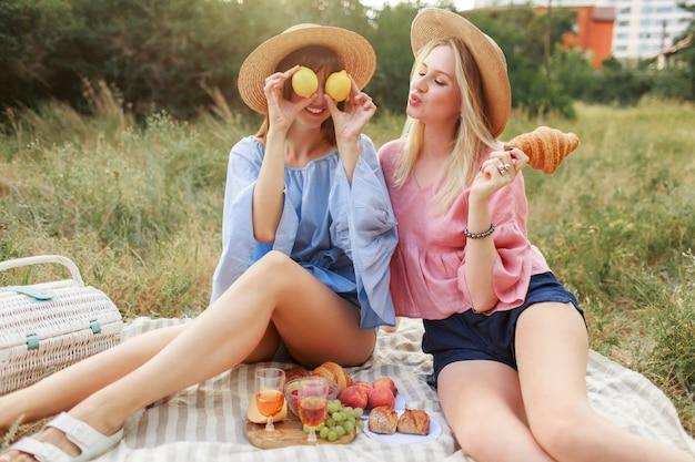 Duas lindas mulheres bonitas posando no gramado no parque de verão, apreciando a comida saborosa, croissants e vinho. amigos fazendo piquenique. Foto gratuita