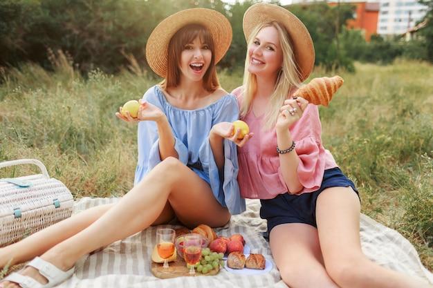 Duas lindas mulheres brincalhonas posando no gramado no parque de verão, apreciando a comida saborosa, croissants e vinho. Foto gratuita