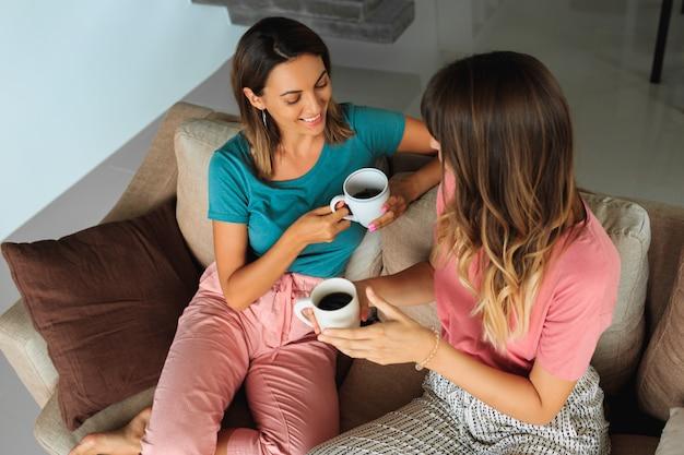 Duas lindas mulheres conversando e tomando chá, enquanto está sentado no sofá na casa moderna Foto gratuita