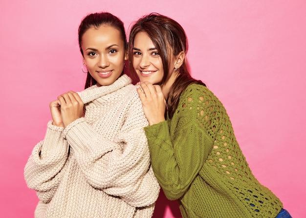 Duas lindas mulheres lindas sorridentes. mulheres em camisolas brancas e verdes elegantes, na parede rosa. Foto gratuita