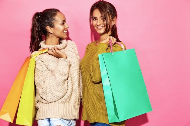 Duas lindas mulheres lindas sorridentes. mulheres que estão nas camisolas brancas e verdes à moda que guardam sacos de compras, na parede cor-de-rosa. Foto gratuita