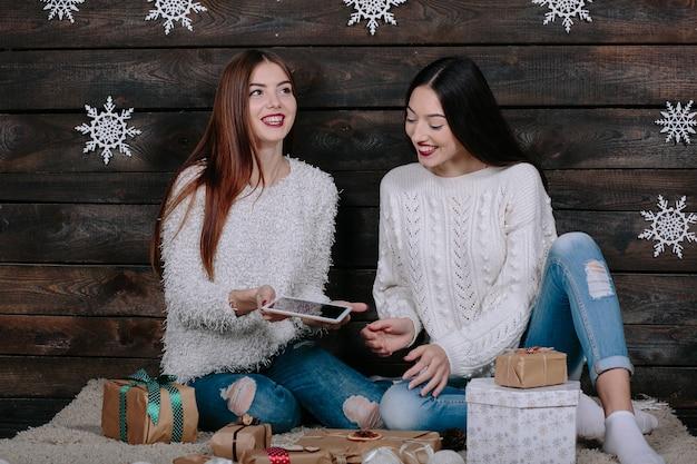 Duas lindas mulheres sentadas no chão com um tablet, entre os presentes de natal Foto gratuita
