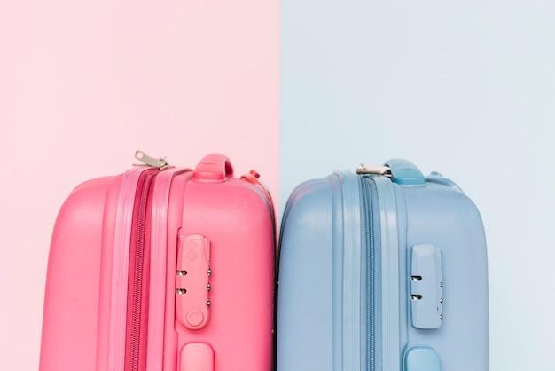 Duas malas de bagagem de plástico azul e rosa em fundo duplo Foto gratuita