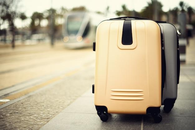 Duas malas de viagem que estão na estação de trem contra o trem da cidade. Foto Premium
