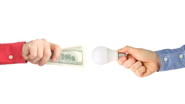 Duas mãos com notas de dólar e uma lâmpada led em branco. Foto Premium