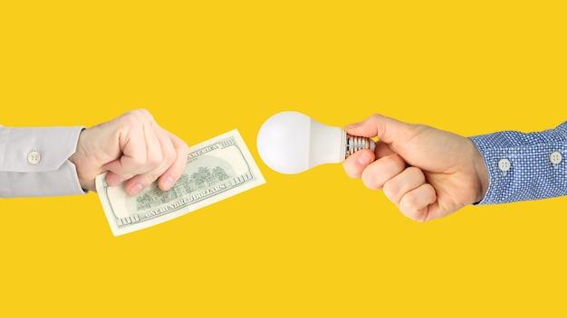 Duas mãos com notas de dólar e uma lâmpada led em um fundo laranja brilhante. pagamento de eletricidade. compre lâmpada led. indústria de negócios Foto Premium