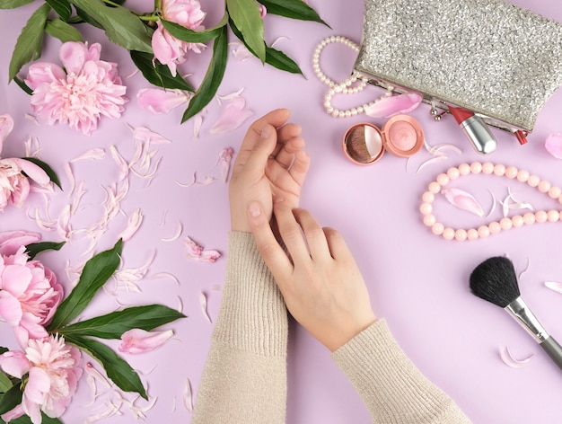 Duas mãos, com, pele lisa, de, um, menina jovem, e, um, bolsa, com, cosméticos Foto Premium