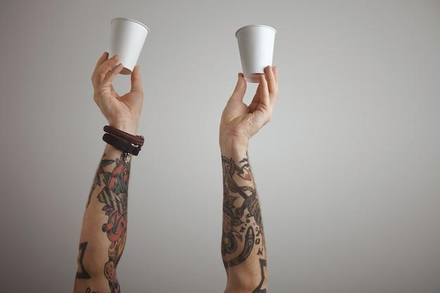 Duas mãos de homens tatuados brutais seguram um papel em branco e levam embora o vidro de papelão no ar. Foto gratuita