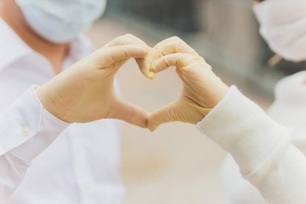 Duas mãos de um casal em luvas de plástico, abraçados. Foto Premium