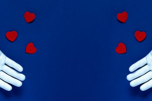 Duas mãos jogam corações vermelhos sobre um fundo azul. o conceito para o dia dos namorados Foto Premium