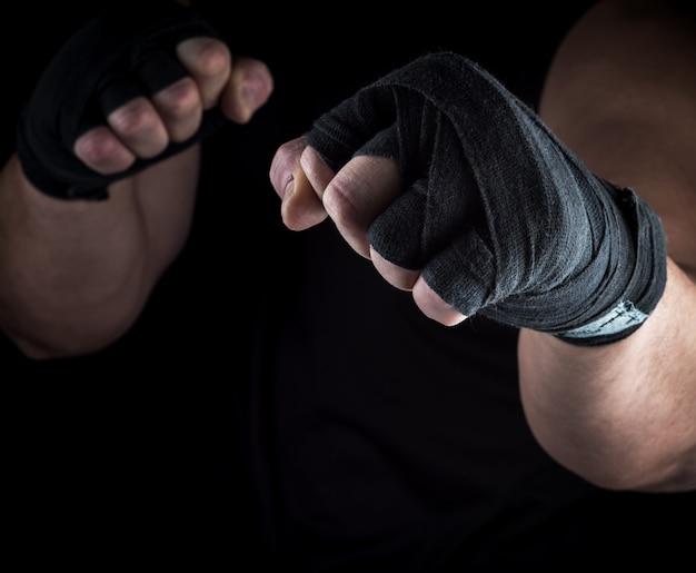 Duas mãos masculinas rebobinadas com uma faixa preta de tecido Foto Premium
