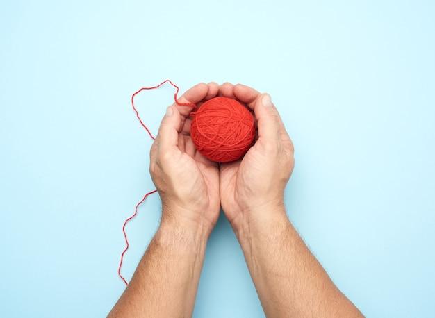 Duas mãos masculinas segurando uma bola de fios de lã vermelha, vista superior Foto Premium