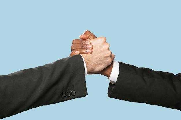 Duas mãos masculinas tremendo isoladas em azul. Foto gratuita