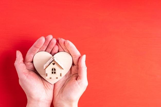 Duas mãos seguram a forma de um coração de madeira e um símbolo de casa de madeira da família, do amor e dos relacionamentos Foto Premium