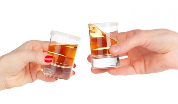 Duas mãos tinindo tiros de bebida alcoólica juntos Foto Premium
