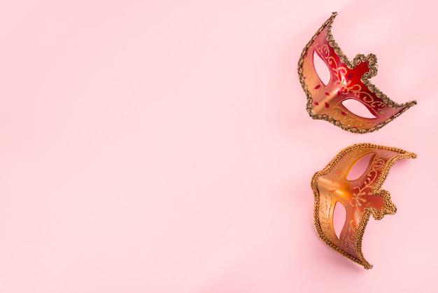 Duas máscaras de carnaval na mesa-de-rosa Foto gratuita