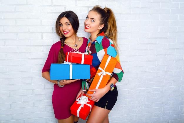 Duas melhores amigas felizes segurando presentes e presentes brilhantes Foto gratuita