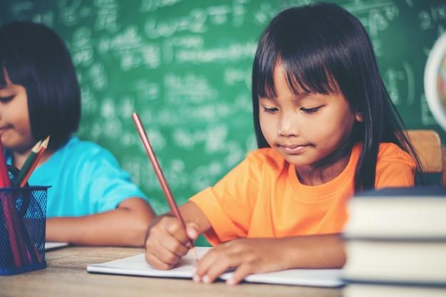 Duas menina com lápis de desenho na aula na sala de aula Foto gratuita