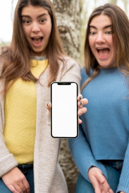 Duas meninas, apresentando, smartphone, mockup Foto gratuita