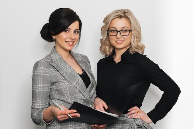 Duas meninas bem sucedidas secretário em ternos de negócio que sorriem com originais. Foto Premium