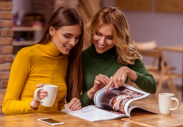 Duas meninas bonitas estão se comunicando, lendo revista. Foto Premium