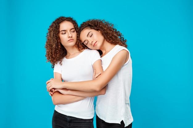 Duas meninas bonitas jovens gêmeas abraçando, sorrindo sobre parede azul Foto gratuita