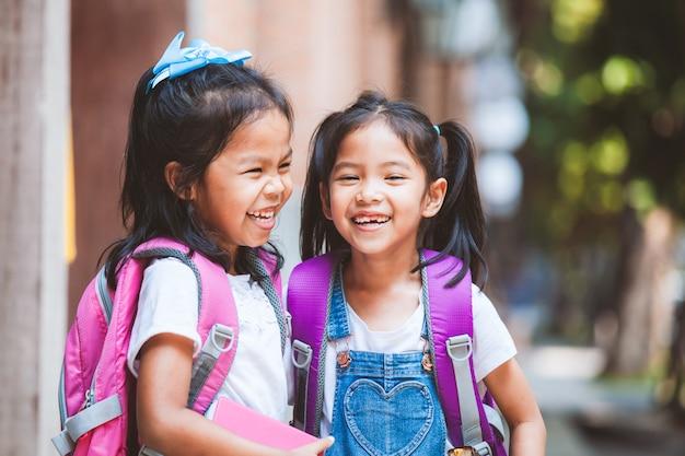 Duas meninas bonito criança asiática com mochila segurando um livro e falando juntos na escola Foto Premium