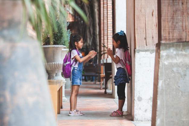 Duas meninas bonito criança asiática com mochila tocando juntos depois da escola na escola Foto Premium