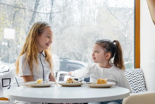 Duas meninas bonitos estão sentados em um café e jogando em um dia ensolarado. recreação e estilo de vida. Foto Premium