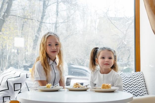 Duas meninas bonitos estão sentados em um café e jogando em um dia ensolarado. Foto Premium