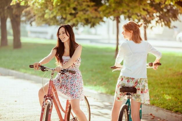 Duas meninas com bicicletas no parque Foto gratuita