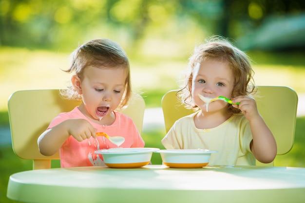 Duas meninas de 2 anos de idade, sentado em uma mesa e comendo juntos contra um gramado verde Foto gratuita