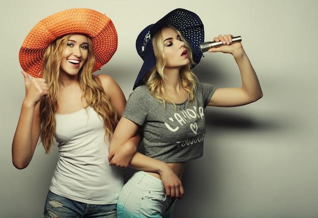 Duas meninas de beleza com um microfone Foto Premium
