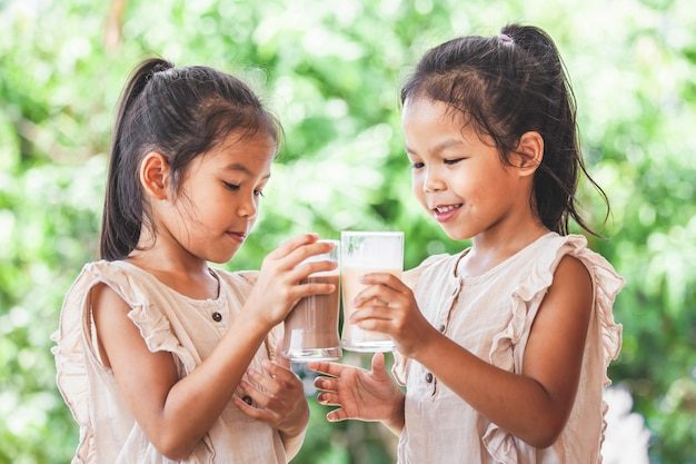 Duas meninas de criança asiática bonito bebendo um leite de vidro juntos Foto Premium