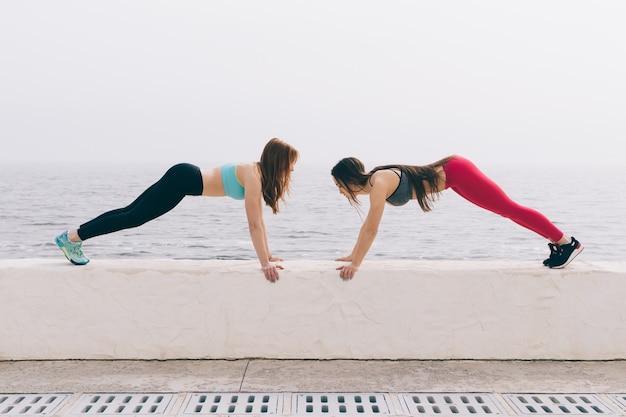 Duas meninas de esportes fazendo esporte exercícios na praia pela manhã. Foto Premium