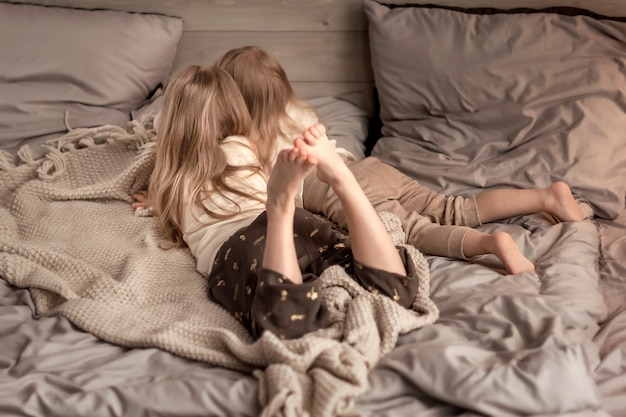 Duas meninas, deitado na cama no quarto Foto Premium