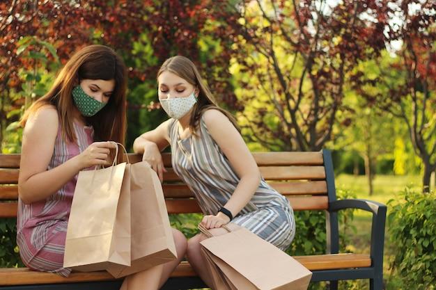 Duas meninas elegantes e atraentes em máscaras protetoras com sacos depois de fazer compras, sentado no parque Foto Premium