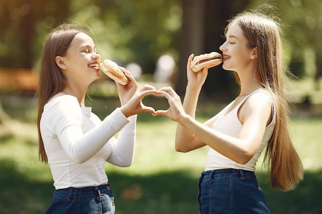 Duas meninas elegantes e com estilo em um parque primavera Foto gratuita