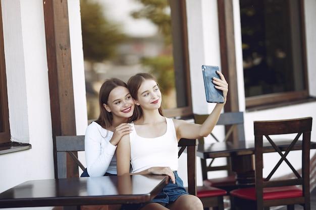 Duas meninas elegantes e elegantes em um café de verão Foto gratuita