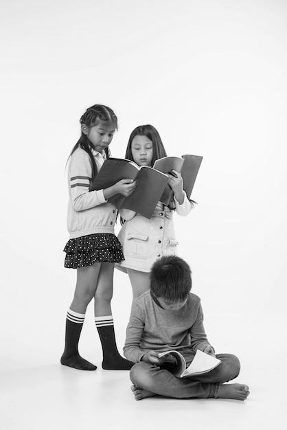 Duas meninas em pé na parte de trás do jovem rapaz. eles estão lendo livros, com sentimento interessado, tom preto e branco. Foto Premium