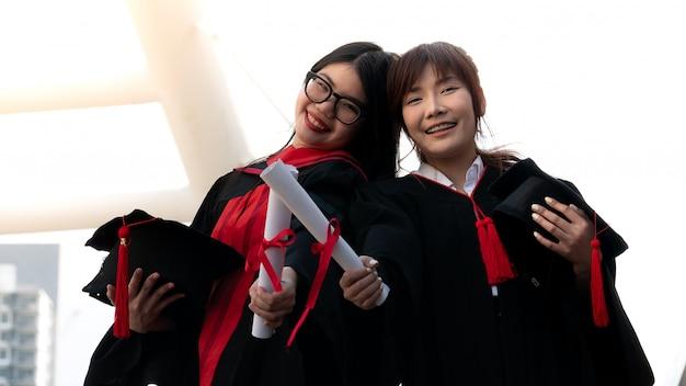 Duas meninas em vestidos pretos e certificado do diploma da preensão que sorriem com graduado feliz. Foto Premium