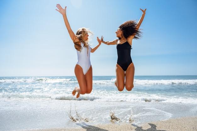 Duas meninas engraçadas com corpos bonitos no roupa de banho que saltam em uma praia tropical. Foto gratuita
